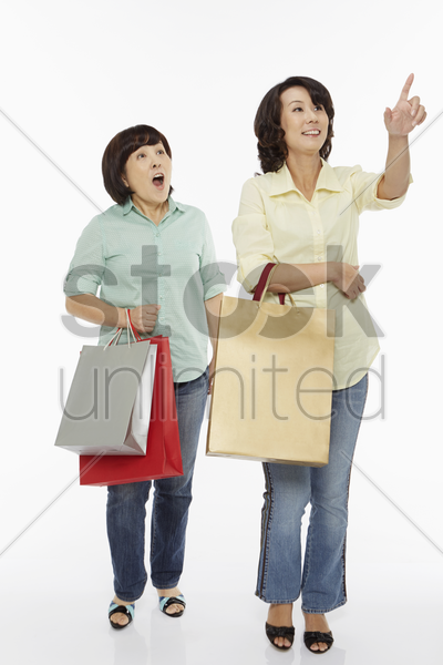 women pointing and looking away from the camera stock photo