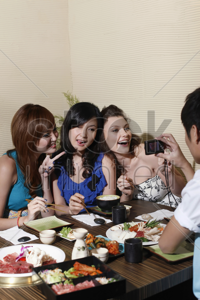 women posing, man taking their picture stock photo