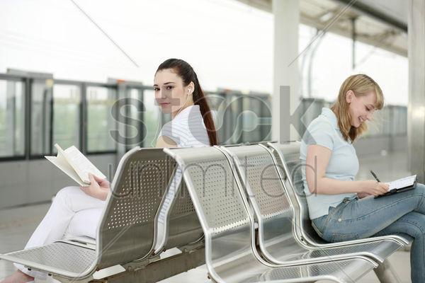 women reading book and writing in organizer while waiting for train to arrive stock photo