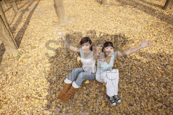 women sitting and throwing dried leaves in the air stock photo