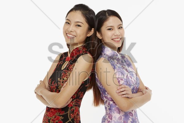 women standing with their backs facing each other stock photo