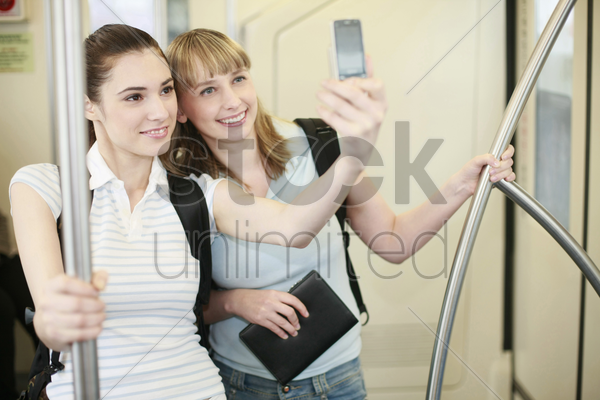 women taking picture of themselves using camera phone stock photo