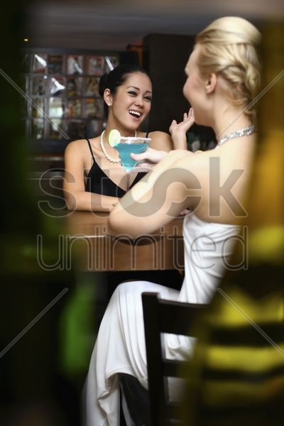women talking and laughing in a bar stock photo