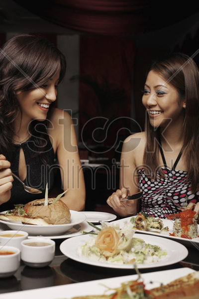women talking over a meal stock photo