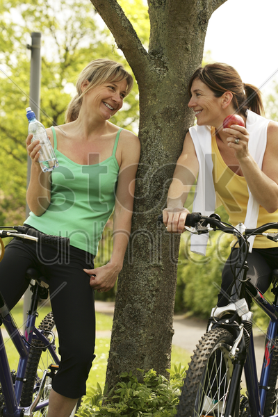 women talking while sitting on bicycles stock photo