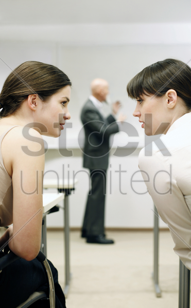 women talking while their lecturer is teaching stock photo