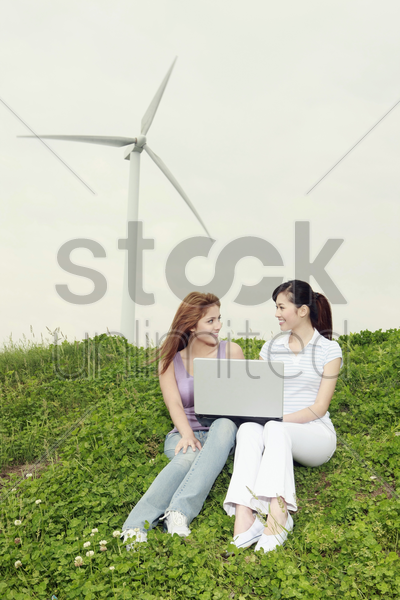 women using laptop outdoors stock photo