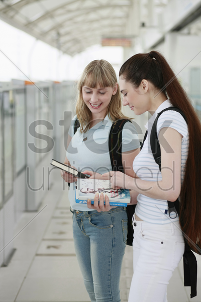women waiting for train to arrive stock photo