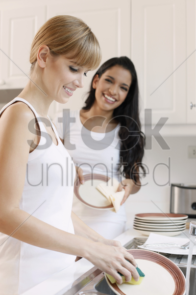 women washing dishes in the kitchen stock photo