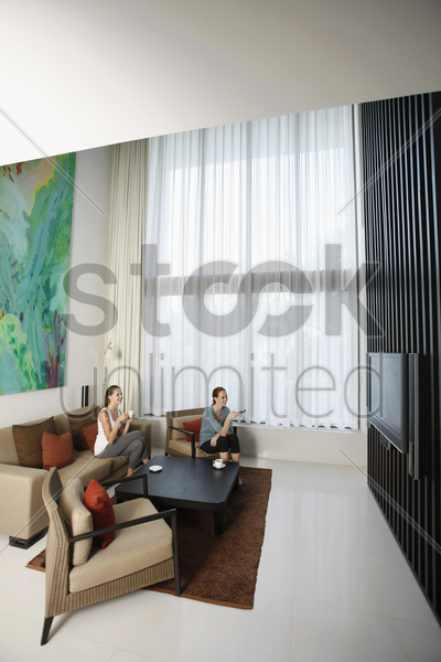 women watching television together stock photo