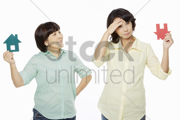women with different facial expressions holding up a cut out house stock photo