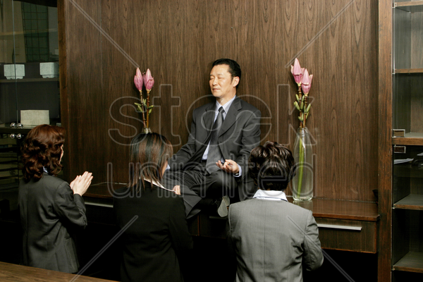 women worshipping a businessman who is sitting on the shelf meditating stock photo