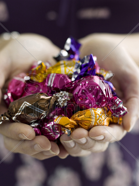 wrapped chocolates in hand stock photo