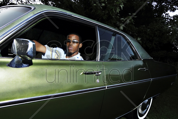 young adult sitting in an old fashion car stock photo
