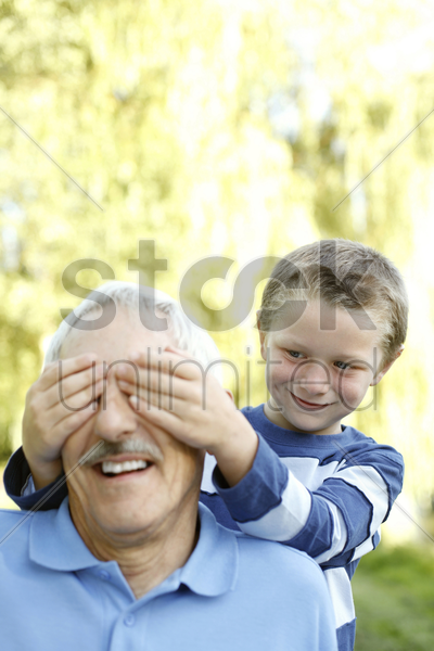 young boy covering his grandfather's eyes stock photo