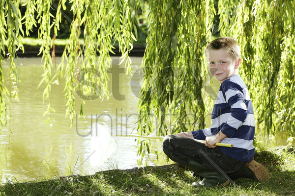 young boy sitting by the lake side holding fishing net stock photo