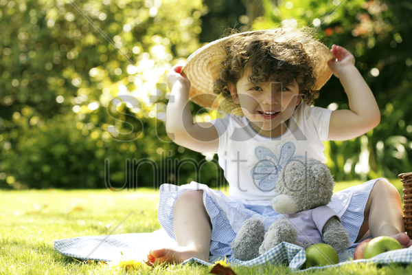 young girl playing with hat while picnicking in the park stock photo