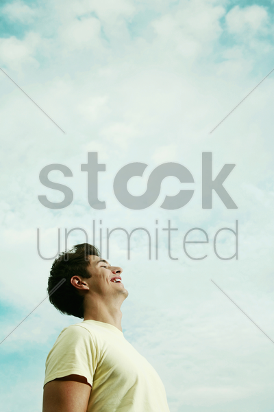 young man laughing while looking up stock photo