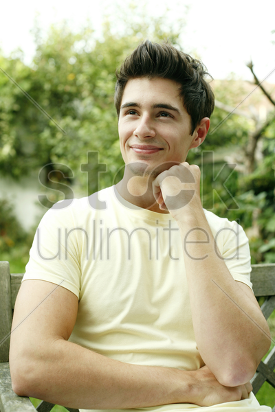 young man sitting on the bench daydreaming stock photo