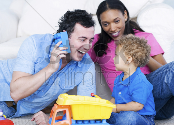 young parents playing with their son stock photo