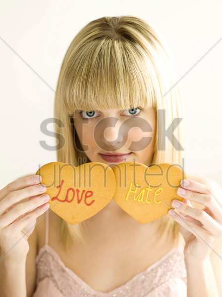 young teen holding two cookies, love and hate stock photo