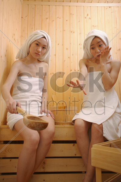 young woman about to pour water on coal, another woman stopping her stock photo
