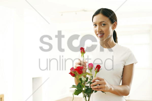 young woman arranging flowers in a vase stock photo