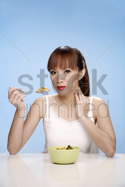 young woman enjoying a bowl of breakfast cereal stock photo