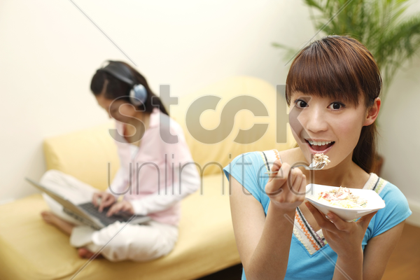 young woman enjoying her food, another woman listening to music and using laptop stock photo