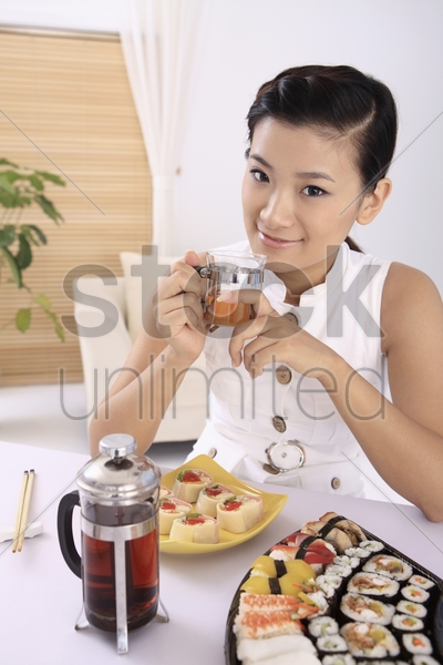 young woman holding a glass of tea, a variant of sushi on the table stock photo