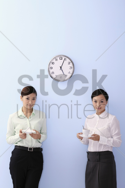 young woman holding a plate of sugar cubes, another woman holding a cup of coffee stock photo