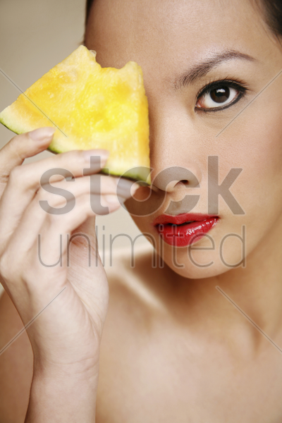 young woman holding a slice of yellow water-melon stock photo