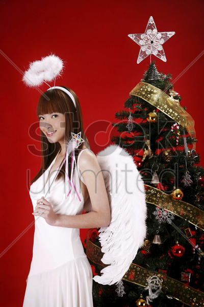 young woman in angel costume standing beside christmas tree stock photo
