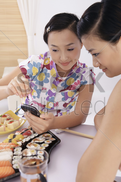 young woman showing text message on her cellphone to her friend stock photo
