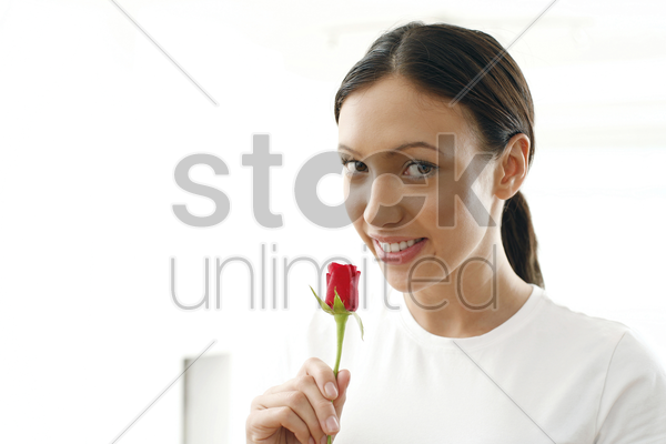 young woman smelling rose stock photo