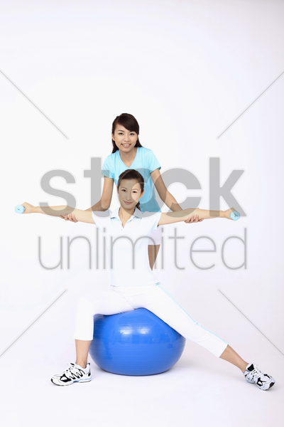 young woman using dumbbells while sitting on fitness ball, another woman helping stock photo
