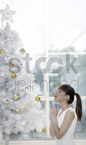 young woman wishing upon a christmas tree stock photo