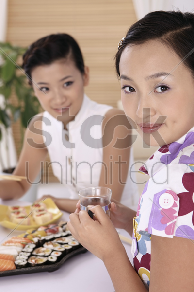young woman with a glass of tea, another woman eating sushi in the background stock photo