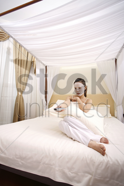 young woman with facial mask watching television stock photo