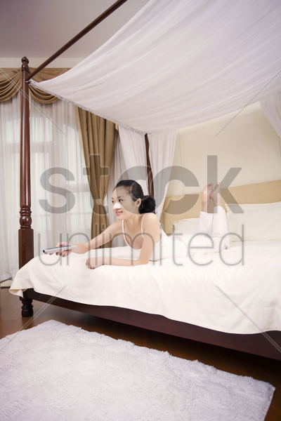young woman with nose strip on her nose lying forward on the bed watching television stock photo
