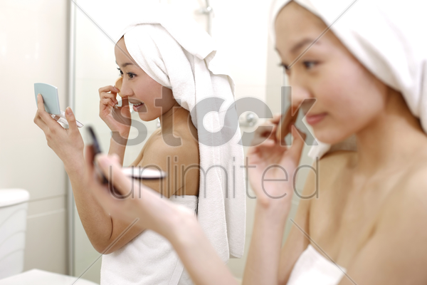 young women applying make-up stock photo