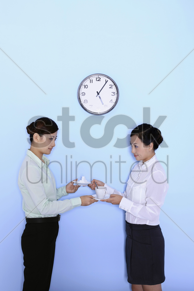young women exchanging sugar cubes and a cup of coffee stock photo