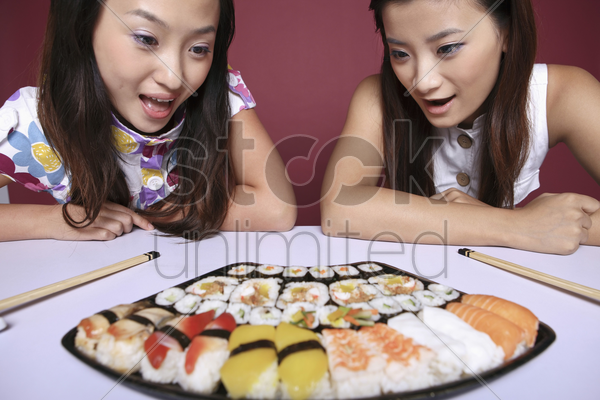 young women looking at the variant of sushi with their mouths opened stock photo