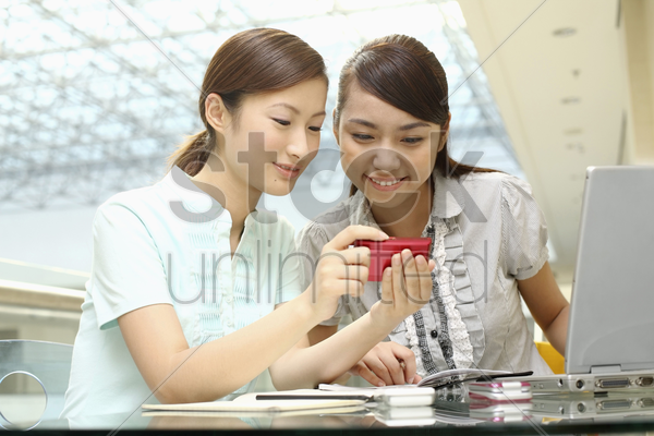 young women looking at their picture on camera stock photo