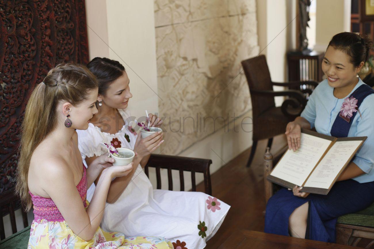 customer service representative explaining about choices of spa customer service representative explaining about choices of spa while women enjoy their tea stock photo