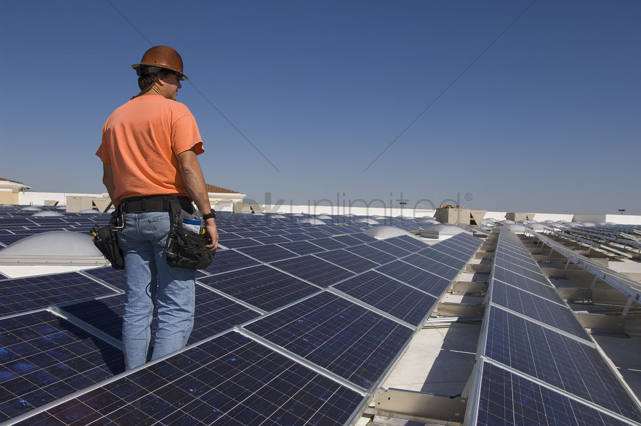 Electrical Engineer Among Solar Panels At Solar Power