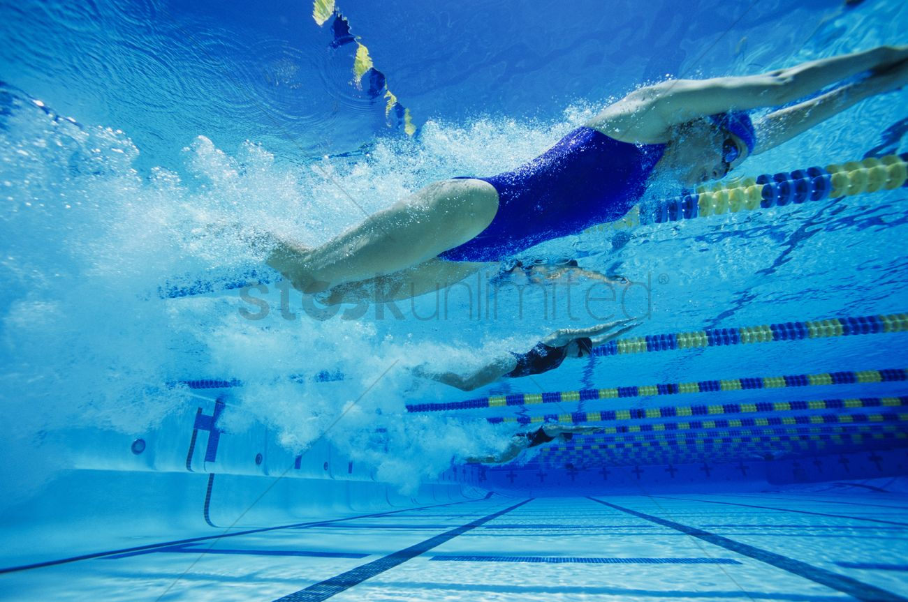 Female swimmers racing underwater in pool stock photo for Swimming images