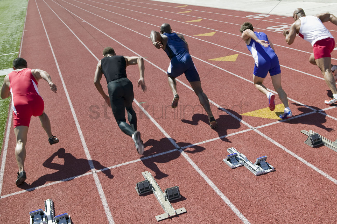 Male sprinters leaving starting blocks Stock Photo ...